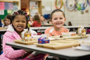 Two elementary school girls eat lunch together.