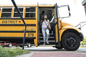 Girl stepping off of school bus