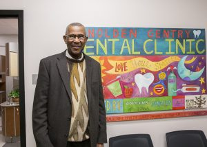 Nolden Gentry stands next to a sign welcoming people to the dental clinic named in his honor at Scavo High School.