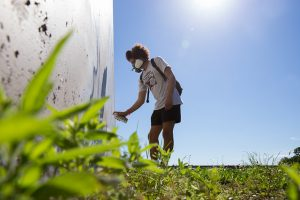 A student works on the recreation of the Urban Leadership program's graffiti art mural on a flood wall along the Raccoon River.