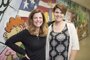 Two women standing in school hallway