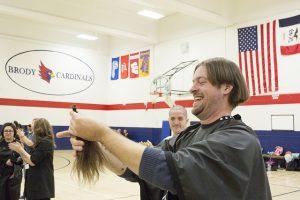 Teacher holding locks of hair.