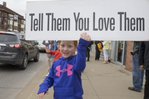 Girls holds sign that read tell them you love them