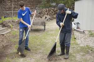 Student and man raking leaves
