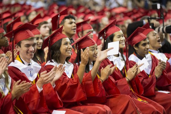 Graduates in red robes applauding