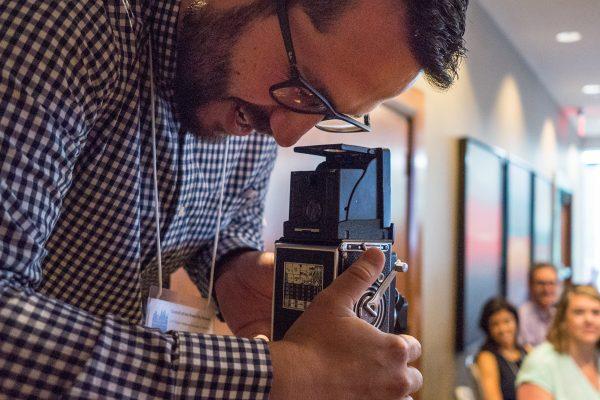 man looking into camera viewfinder
